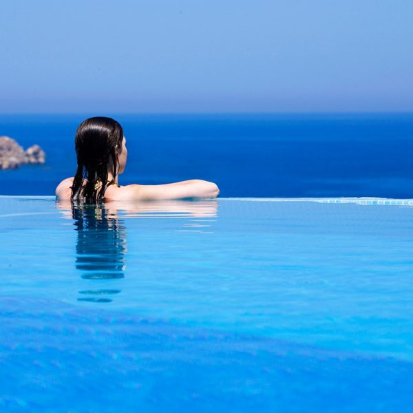 Woman rests on the edge of the sea view private pool at the Yria Hotel Luxury Villa rental in Paros